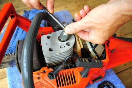 Réparation d'une tronçonneuse avec une clé à bougie