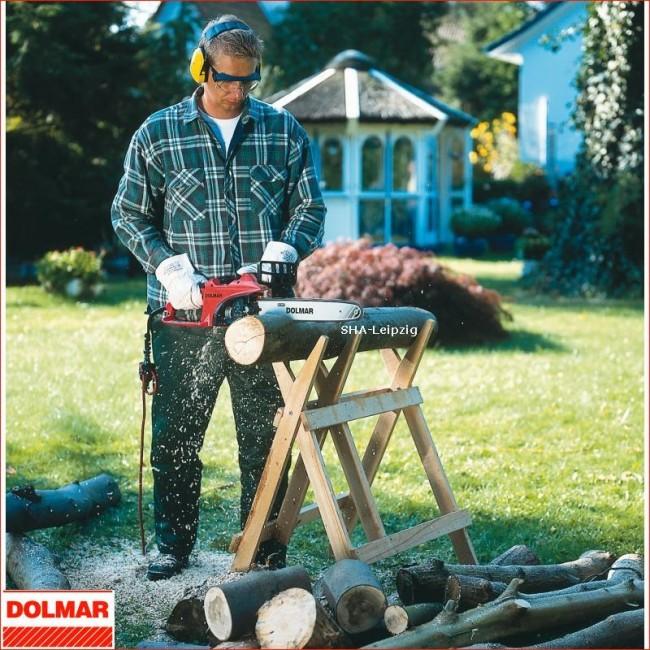 Homme tronçonnant une bûche avec une tronçonneuse Dolmar électrique